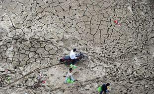 Des Indiens traversent la zone marécageuse de la rivière Yaumna après le retrait des eaux liée à une crue dans la région de Sangam à Allahabad le 13 septembre 2016.