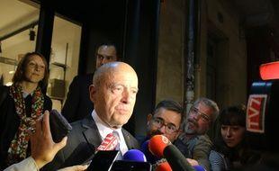 Alain Juppé, à la sortie du magasin «Yvonne» qui a subi des dégradations dans le quartier Saint-Michel
