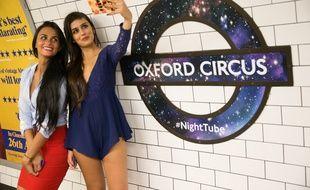Deux jeunes femmes prennent un selfie à la station Oxford Circus du métro de Londres, le 19 août 2016.