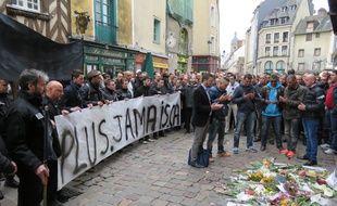 Le cortège composé de proches de la victime et d'agents de sécurité s'est recueilli devant le bar où s'est déroulé le drame.