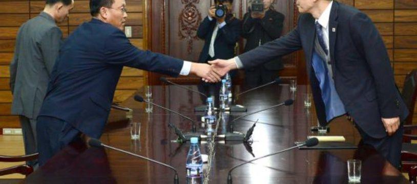 Kim Ki-Woong (d), haut responsable du ministère sud-coréen de l'Unification serre la main de son homologue nord-coréen, lors d'une rencontre à Panmunjom, le 26 novembre 2015 dans la zone démilitarisée entre les deux Corées