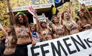 Les Femen devant le Lavoir Moderne à Paris (18e), où elles avaient installé leurs locaux, endommagés par un incendie le 21 juillet 2013