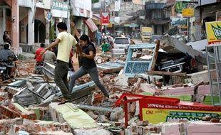 Un couple d'Indonésiens marche dans les décombres de la ville de Padang (Sumatra) le 1er octobre 2009 après le séisme du 30 septembre.