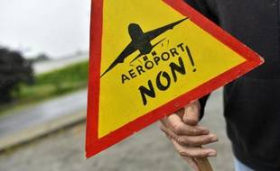 Un militant montre son opposition au transfert del'aéroport de Nantes à Notre-Dame-des-Landes par une pancarte, le 13 juin 2016 à Notre-Dame-des-Landes