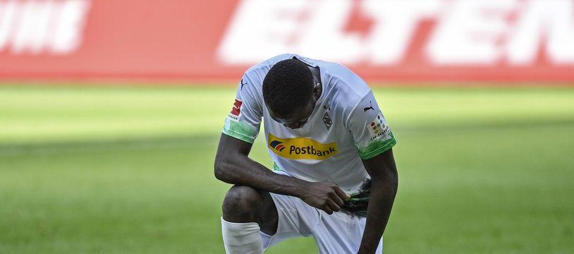 Marcus Thuram, l'attaquant de Moenchengladbach, met un genou à terre en hommage à George Floy après avoir marqué son deuxième but lors du match de Bundesliga entre le Borussia et l'Union Berlin dimanche 31 mai 2020. (AP Photo/Martin Meissner, Pool)/