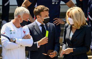 Le président français Emmanuel Macron tient un carton jaune à côté de son épouse Brigitte Macron et du sélectionneur Didier Deschamps au camp d'entraînement de football national de Clairefontaine-en-Yvelines, le jeudi 10 juin 2021.