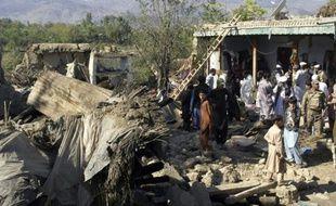 Des policiers et habitants au milieu des ruines de maisons détruites par un puissant séisme, le 27 octobre 2015 à Lower Dir, au Pakistan