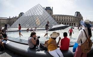 Des touristes devant le musée du Louvre, à Paris, en août 2018.