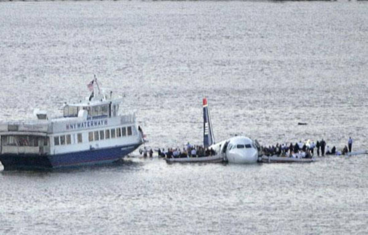 Passengers stand on the wings of a U.S. Airways plane as a ferry pulls up to it after it landed in the Hudson River in New York January 15, 2009. A small plane carrying more than a dozen people splashed down in the frigid waters of the Hudson River off Manhattan on Thursday and survivors were seen standing on the wings awaiting rescue, Reuters witnesses said. REUTERS/Gary Hershorn (UNITED STATES) – REUTERS/Gary Hershorn