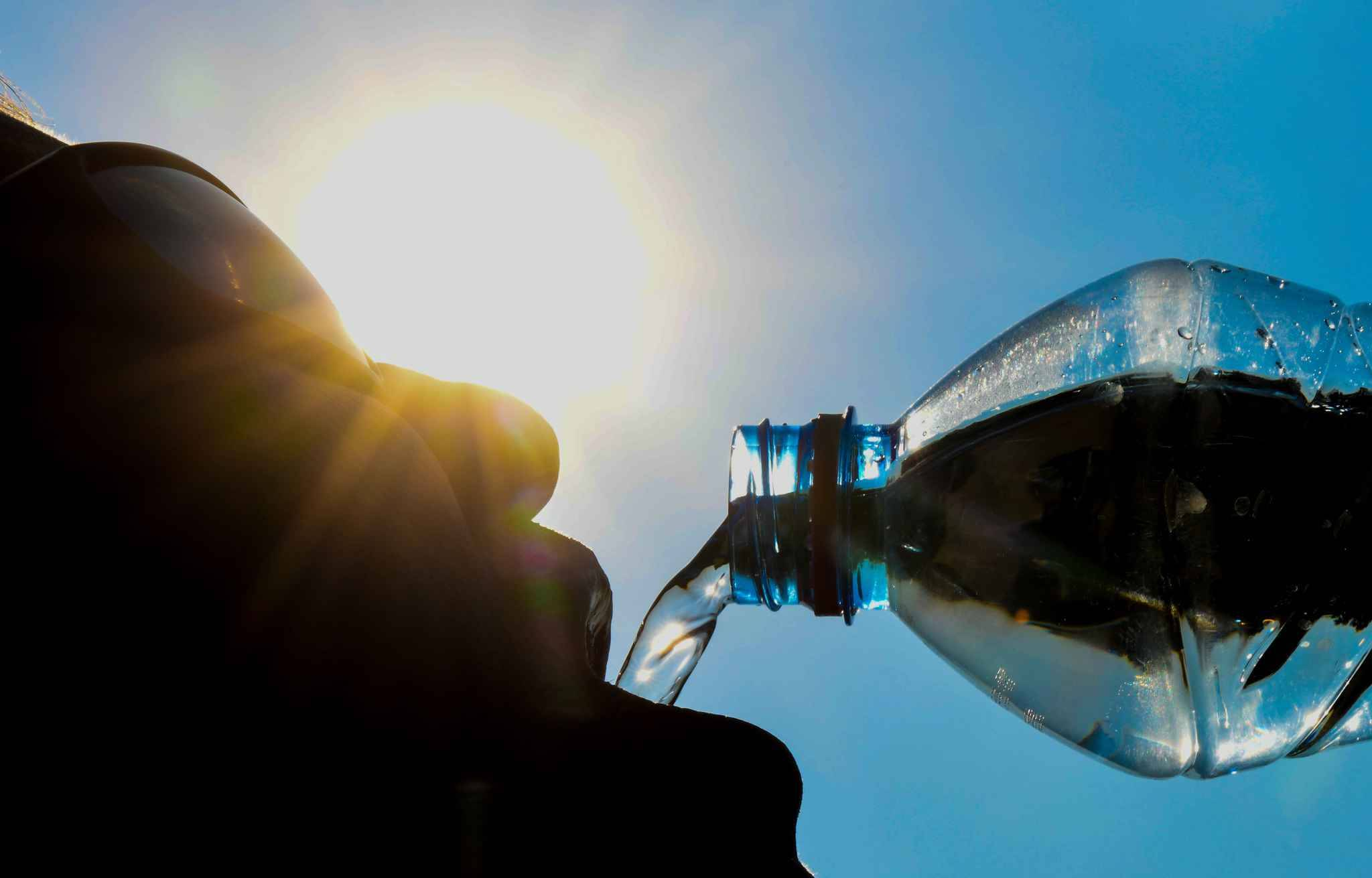 A man poses while drinking from a water bottle as the sun shines in the northern French city of Lille on July 25, 2018.   Some 18 departments across France have been placed on an 'orange' alert as heatwave conditions prevail across western Europe.