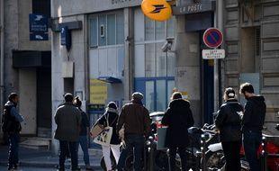 Des clients attendent de pouvoir entrer dans leur bureau de poste, à Paris, resté ouvert pendant le confinement.