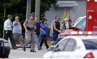 Un policier accompagne les parents venus récupérer leurs enfants après qu'une voiture a percuté une garderie en Floride, le 9 avril 2014.