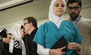 Namee Barakat (2e g), le père d'un des trois étudiants musulmans tués, embrasse sa femme, tandis que sa fille (2e d) et d'autres personnes quittent leur conférence de presse, le 11 février 2015 à Chapel Hill