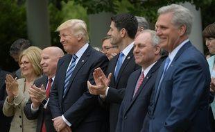 Le président américain Donald Trump avec à ses côtés le président de la Chambre des représentants, Paul Ryan, célèbrent leur victoire contre l'Obamacare dans la roseraie de la Maison Blanche, le 4 mai 2017.