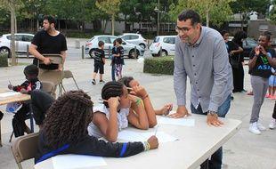 Rachid Santaki détend les jeunes qui participent à la Dictée des cités à Saint-Denis.