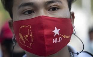 Un masque aux couleurs du parti d'Aung San Suu Kyi, et avec son visage.