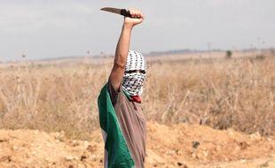 Un manifestant palestinien brandit un couteau lors de heurts avec l'armée israélienne vendredi 9 octobre dans la ville de Gaza.