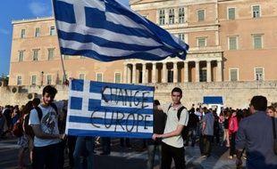 Des manifestants grecs brandissent un drapeau grec pour demander de changer l'Europe, le 29 juin 2015, en face du parlement, dans le centre d'Athènes