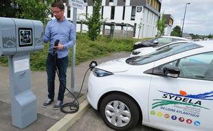 Un véhicule électrique du Sydela devant une borne de recharge.