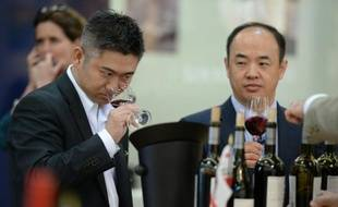 Des visiteurs goûtent un vin rouge lors du salon Vinexpo à Bordeaux, le 15 juin 2015