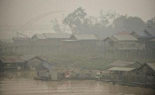 Des habitants de Palangkaraya, touchée par l'épaisse fumée toxique des feux de forêts en Indonésie, près du fleuve Kahayan, le 25 octobre 2015