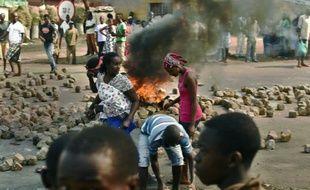 Des burundaises près d'une barricade en feu, à Bujumbura le 21 juillet 2015