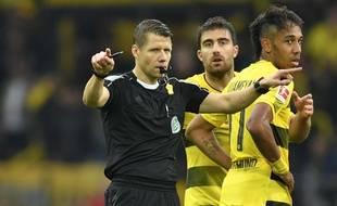 Un arbitre allemand sollicitant la VAR pendant le match Dortmund-Cologne