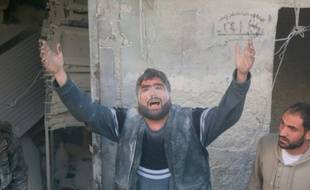 Un Syrien appelle à l'aide après un raid aérien contre une zone d'Alep détenue par les rebelles, le 11 mars 2016