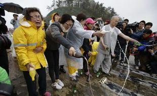Un moine bouddhiste et des proches des passagers prient lors d'une cérémonie à Jindo, au sud de Séoul, le 18 avril 2014.