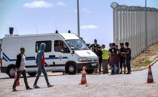 Des migrants et des policiers dans la Jungle de Calais, près de la rocade portuaire.