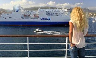 """Une femme contemple le ferry de la SNCM """"Paglia Orba"""" depuis un bateau de Corsica Ferries, le 10 juillet 2014 dans le port d'Ajaccio"""