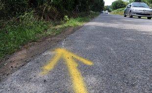 Une flèche jaune réalisé par les forces de l'ordre montrant le lieu exact de l'accident de voiture dans le Morbihan qui a coûté la vie à quatre adolescents.