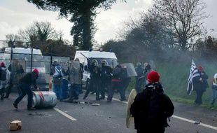 """Des manifestants """"bonnets rouges"""" affrontent la police à côté d'un portique d'écotaxe en Bretagne, le 15 février 2014"""
