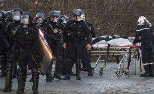 """Des pompiers prennent en charge un policier blessé, samedi 5 décembre 2020, en marge d'une manifestation contre la PPL """"Sécurité Globale"""", à Nantes."""