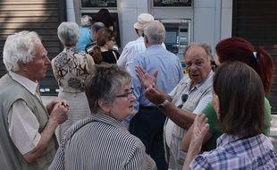 Le 30 juin 2015, à Athènes (Grèce), des retraités discutent politique tout en faisant la queue devant des distributeurs de billets.