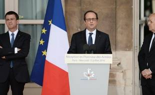Le président François Hollande, entouré du Premier ministre Manuel Valls (G) et du ministre de la Défense Jean-Yves Le Drian (D), le 13 juillet 2016 à Paris