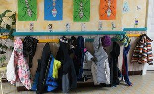 Des manteaux accrochés à l'extérieur d'une salle de classe (image d'illustration).
