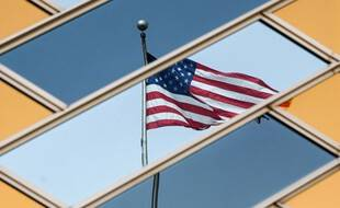 Le drapeau national américain se reflète sur les fenêtres du bâtiment de l'ambassade américaine à Kaboul le 30 juillet 2021.