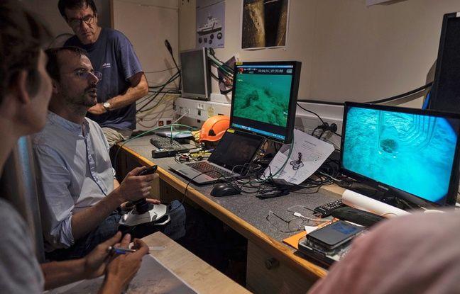 Des techniciens dirigent le robot sur les épaves
