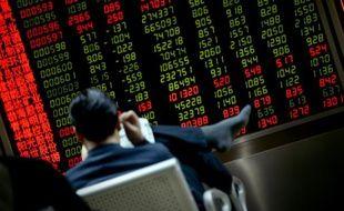 Un investisseur lit un journal devant un écran de cotation à Pékin le 20 janvier 2016