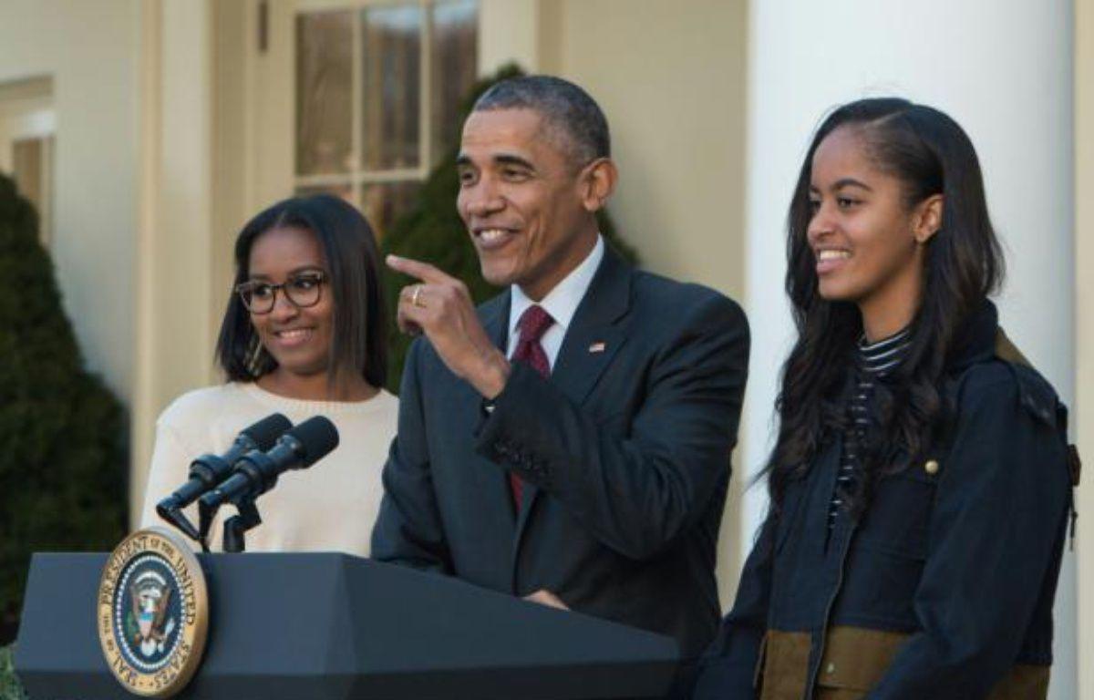 Barack Obama, entouré de ses filles Malia (d) et Sasha (g), le 25 novembre 2015, à Washington DC – NICHOLAS KAMM AFP