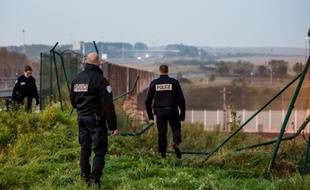 Des agents de sécurité inspectent la clôture endommagée par des migrants qui ont pénétré dans le tunnel sous la Manche à Coquelles, dans le Pas-de-Calais, le 3 octobre 2015