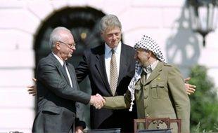 Poignée de mains historique entre le Premier ministre israélien Yitzahk Rabin (d) et le chef de l'OLP Yasser Arafat, sous les yeux du président américain Bill Clinton (c), à la Maison Blanche le 13 septembre 1993