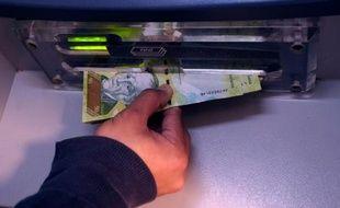Une personne retire de l'argent à un distributeur à Caracas