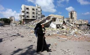 Une femme palestinienne passe devant les décombres du centre culturel Said al-Mishal, dans la ville de Gaza, détruit une attaque aérienne israélienne le  11 août 2018.