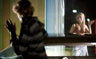 Une jeune femme fait un signe d'aurevoir à un homme.