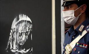 L'oeuvre attribuée à Banksy en hommage aux victimes du Bataclan, à Rome le 11 juin 2020 devant un carabinier italien.