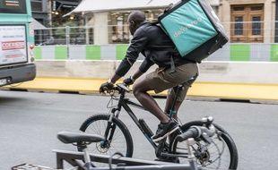 Un livreur à vélo, travaillant pour la plateforme Deliveroo, rue de Rivoli à Paris.