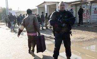 Calais (Pas-de-Calais), le 23 octobre 2016. Un migrant chargé d'une valise passe derrière un policier chargé de la sécurité dans la «jungle».