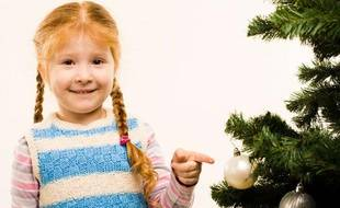 Une petite fille à côté d'un arbre de Noël